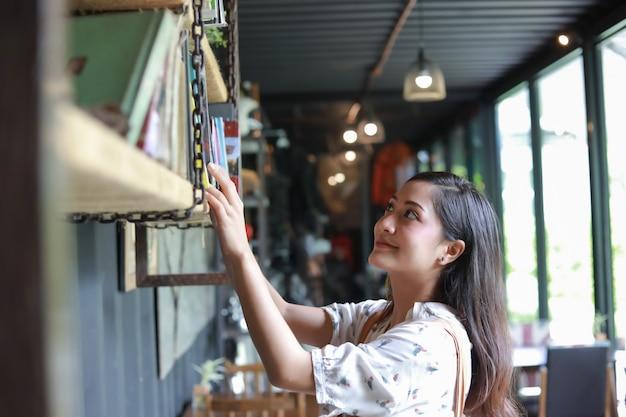 アジアの女性の選択読書と笑顔と幸せのための本喫茶店でリラックス