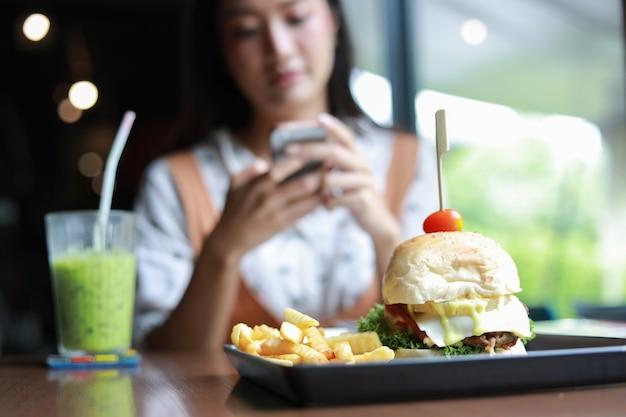アジアの女性の笑顔と幸せとリラックスタイムにコーヒーとレストランでハンバーガーを食べて楽しんで