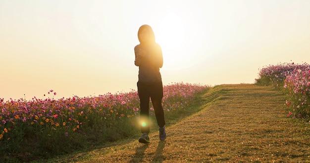 Азиатские женщины бегают по утрам на поле цветов космоса