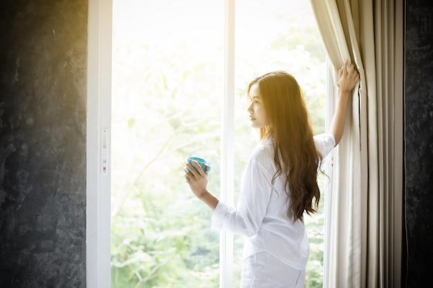 彼女のベッドでコーヒーを飲んで目を覚ますアジアの女性たちは、完全に休息してカーテンを開きます