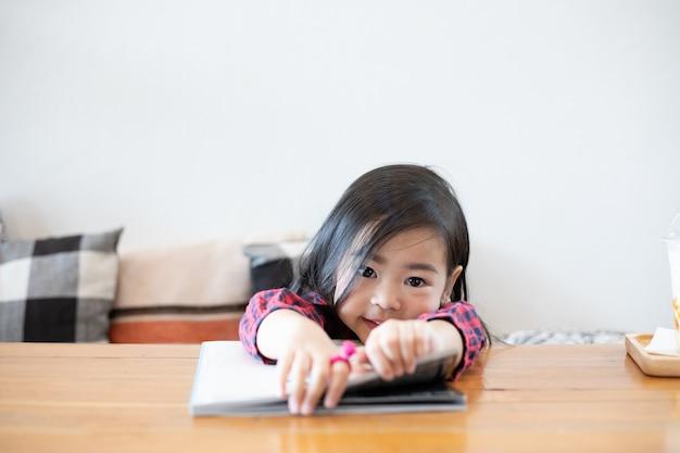 アジアのかわいい女の子は本を読んでいます。