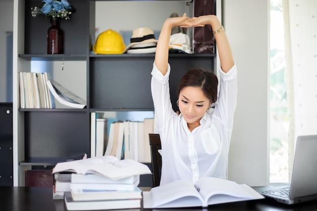 アジアの女性の本を読んだ後ストレッチし、一生懸命働いて、ホームオフィスで笑顔