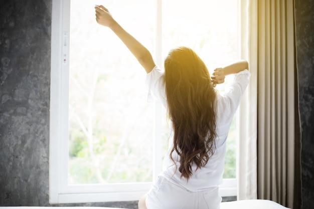 Женщина красивая молодая улыбается, сидя на кровати и растяжения в утро в спальне