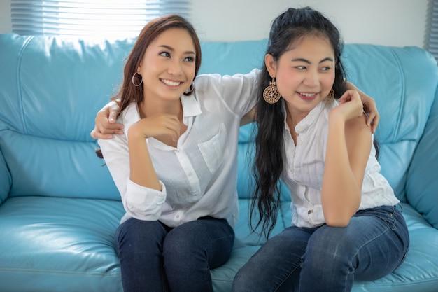 Образ жизни портрет азиатских женщин лучших друзей - улыбающиеся счастливые на диване в гостиной