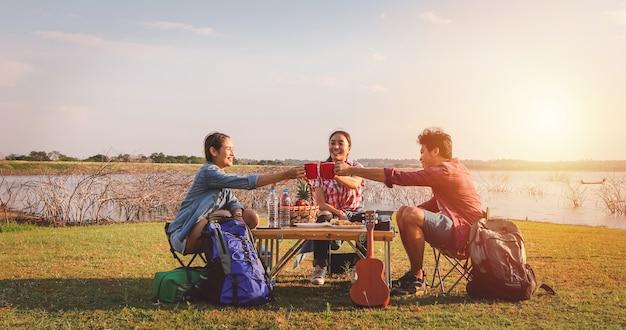 コーヒーを飲みながら、夏休みにピクニックをする時間を過ごすアジアの友人のグループ。彼らは幸せで、休日を楽しんでいます。