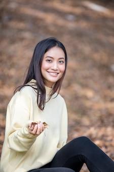 美しいアジアの女性幸せな女の子の笑顔と公園で屋外で暖かい服冬と秋の肖像画を着て