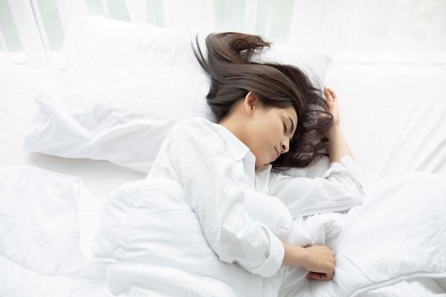 美しいアジアの女性の日向ぼっこと白いベッドで寝ています。