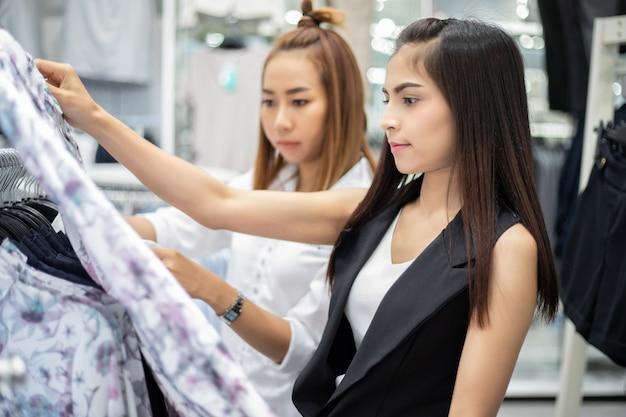 Две улыбающиеся молодые женщины азии с покупками и покупками в торговом центре / супермаркете / рынке