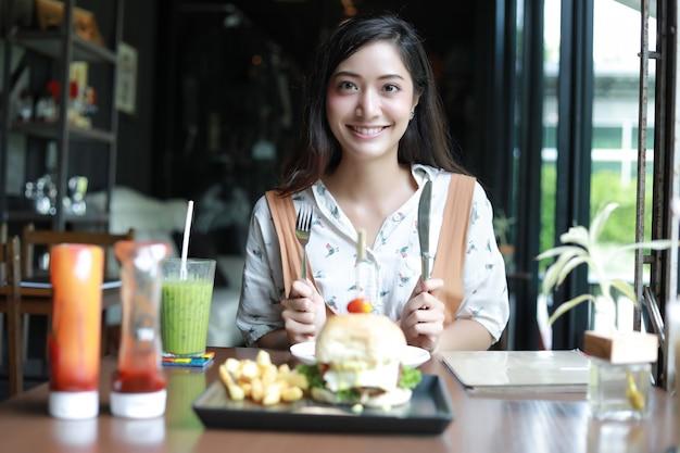 リラックスした時間にコーヒーとレストランでハンバーガーを食べて笑って幸せで楽しんだアジアの女性