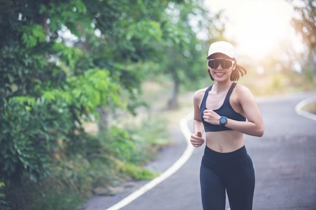 アジアの女性を実行していると都市実行の屋外でジョギング