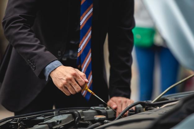 ビジネスマンは、ビジネスウーマンが壊れた車をチェックして修理するのを手伝います