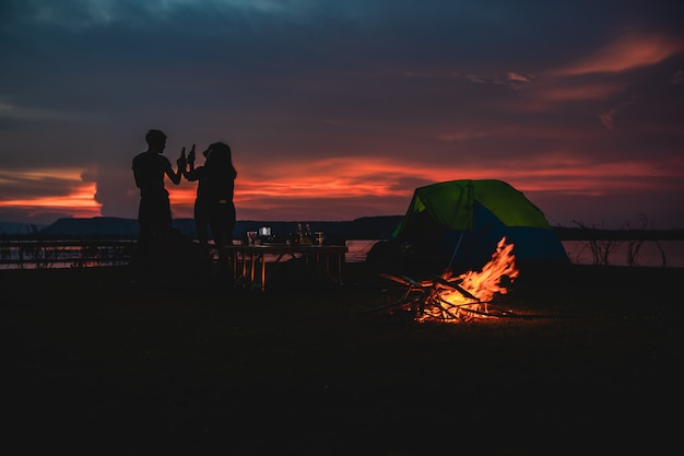 Силуэт группы азиатских друзей туристов, пьющих и играющих на гитаре вместе со счастьем летом во время кемпинга возле озера