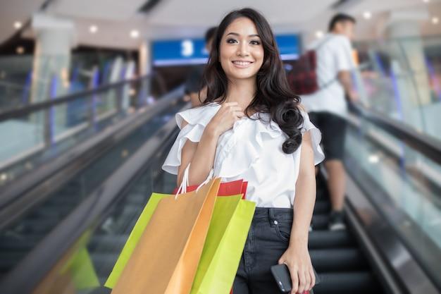 美しい少女は買い物袋を保持しているとスーパー/モールで買い物をしながら笑顔