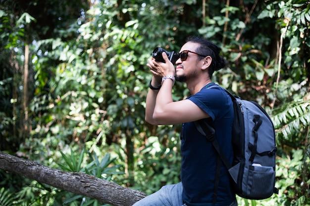 アジアの男性のバックパックと一緒に歩いて幸せな旅行者が森で写真を撮って、休日の概念旅行の時間をリラックス