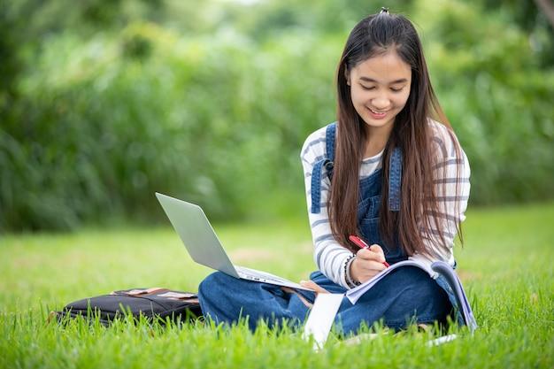 美しいアジアの女子学生の本を保持していると笑顔と夏の公園での学習と教育のリラックス時間