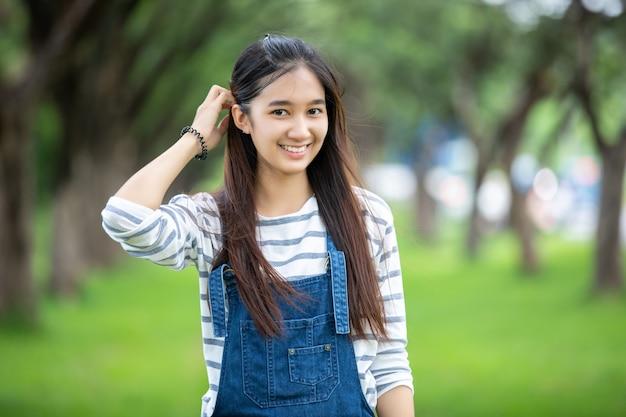 リラックス時間のために夏の公園の木に美しいアジアの少女の笑顔