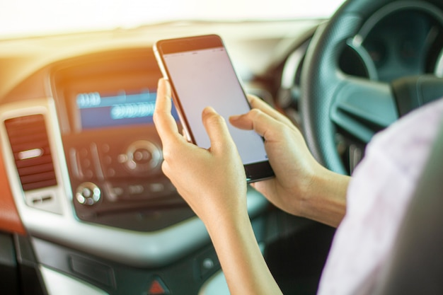 Азиатские женщины за рулем автомобиля и с помощью смартфона на дороге.