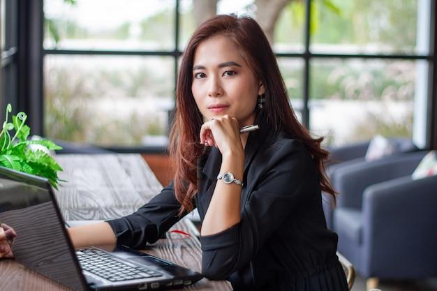 Азиатские бизнес-леди используя тетрадь и умный телефон и бизнес-леди усмехаясь счастливые для работы