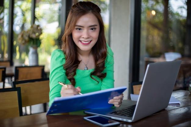 アジアのビジネスウーマン笑顔とノートを使用して分析ドキュメントとグラフの財務図の作業と彼女はコーヒーショップでコーヒーを飲んでいます。