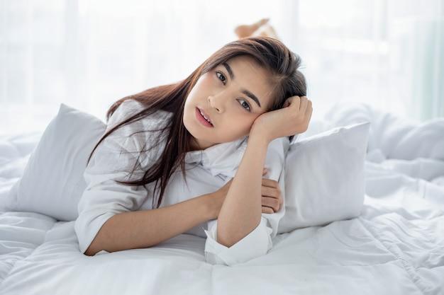 アジアの女性の美しい若い笑顔の女性に座って、白いベッドで寝て、ベッドで目覚めた後、寝室で朝のストレッチを完全に休んだ