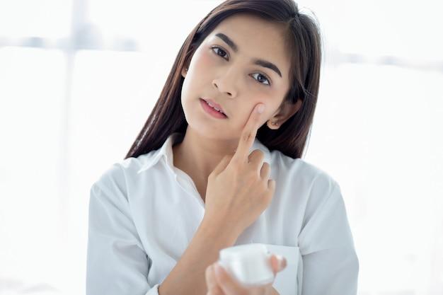 Красивая азиатка с помощью средства по уходу за кожей, увлажняющего крема или лосьона, ухаживающего за ее сухой кожей. увлажняющий крем в женских руках.
