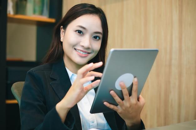 タブレットを使用してオフィスで働くアジアビジネスの女性は、時間をリラックスして笑顔