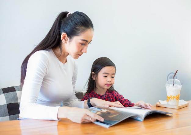 アジアの母親が、リビングテーブルで学期の休憩中に本を読むように娘に教え、自宅のテーブルに冷たい牛乳を置いています。家族の教育概念と活動