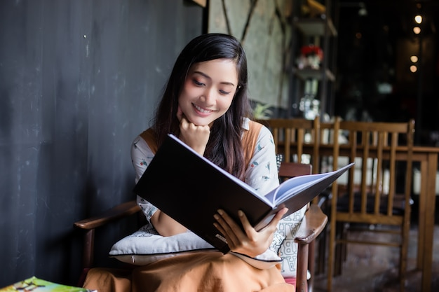 Милая азиатская женщина сидит читает книгу на диване или стул счастливой улыбкой дома во время отдыха