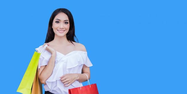 美しいアジアの若い女性は買い物袋を持って立っています。彼女は青色の背景にショッピングモールで幸せを笑顔します。
