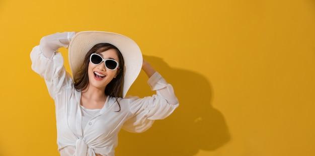 Портрет азиатских красивая счастливая молодая женщина с солнцезащитные очки и шляпу, улыбаясь веселый летом и глядя на камеру, изолированные на фоне желтой студии.