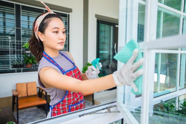 アジアの女性が自宅のガラスのドアとクリーニングテーブルを消毒