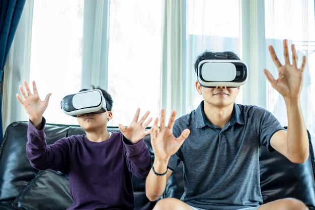 Азиатские папа и сын любят играть в видеоигры вместе с видео джойстиком и очками виртуальной реальности с увлекательным и очень веселым занятием в гостиной дома