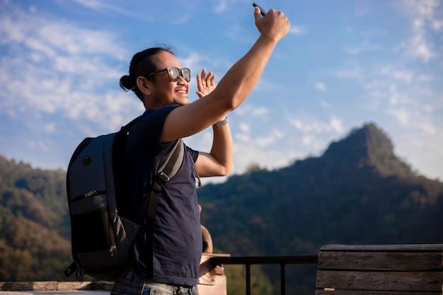 アジア人男性の観光客は、携帯電話を使用して、ソーシャルネットワーキングを介して、ソーシャルメディアで共有されている自分撮りを撮影しています。