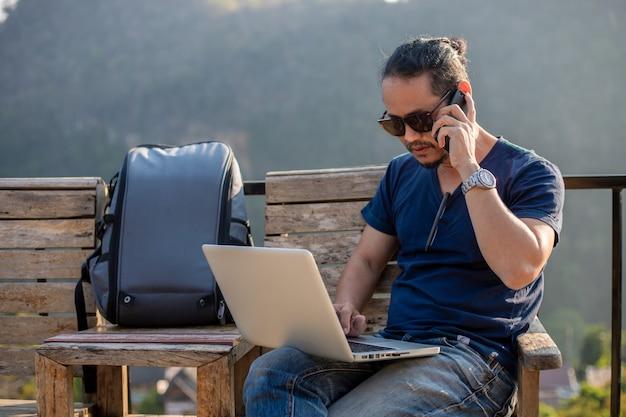アジアの男性のバックパックと屋外の性質でコンピューターのラップトップに取り組んでいる旅行者と彼はリラックスして旅行を楽しんでいます