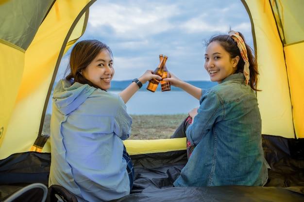Азиатские женщины с друзьями туристами пьют пиво вместе со счастьем летом