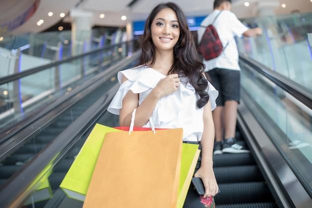 アジアの女性と美人はスーパーマーケット/モールでショッピングバッグを持っています