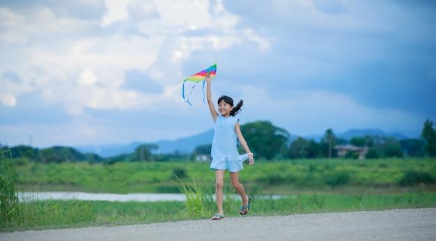 自然の中で夏の草原で幸せと幸せを持つアジアの子供の女の子