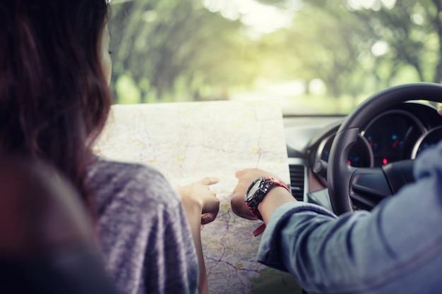 Азиатские мужчина и женщина, используя карту на дороге поездки и счастливый молодая пара с картой в автомобиле. размытые и