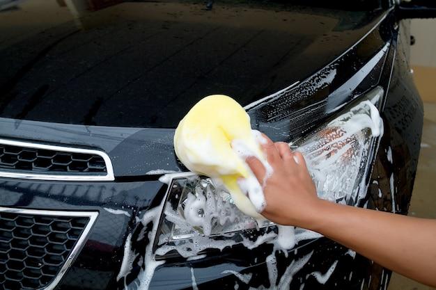 泡を持つ黄色のスポンジを使って車を洗う男の手