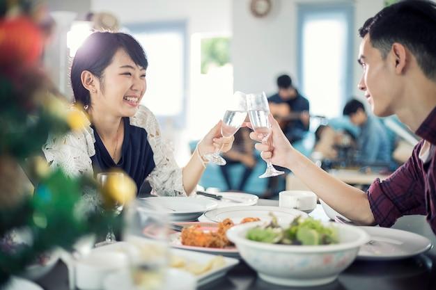 ロマンチックなディナーを楽しむアジアの若いカップルは、夕食のテーブルに座っている間に飲む