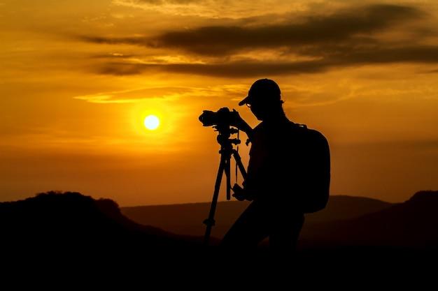 アジアの女性の写真のシルエットは、日没、ソフトフォーカスの山と写真を撮る