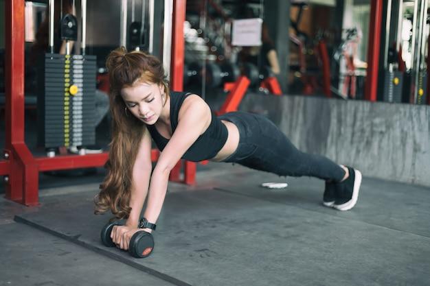 若いフィットネスアジアの女性の運動とダンベルと板張りの位置を行う