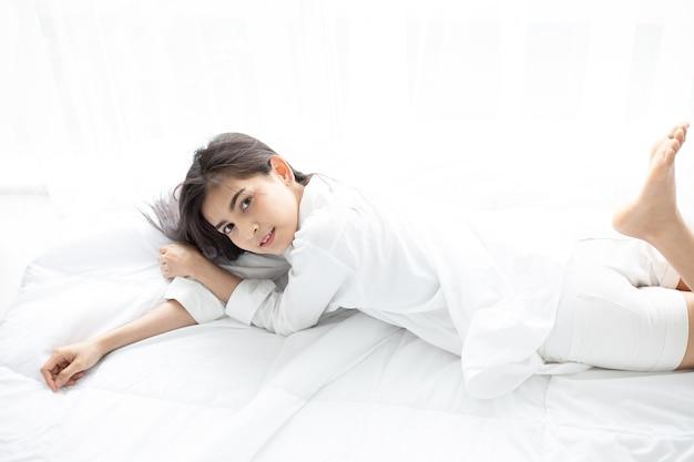 Азиатская женщина красивая молодая женщина улыбается, сидя на кровати и растяжения на утро в