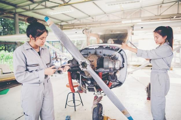 Азиатский студент инженеры и техники ремонтируют самолет по классу в университете