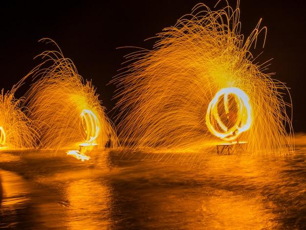 回転するスチールウールから回転する金属の輝く火花の美しいまぶしさと火花