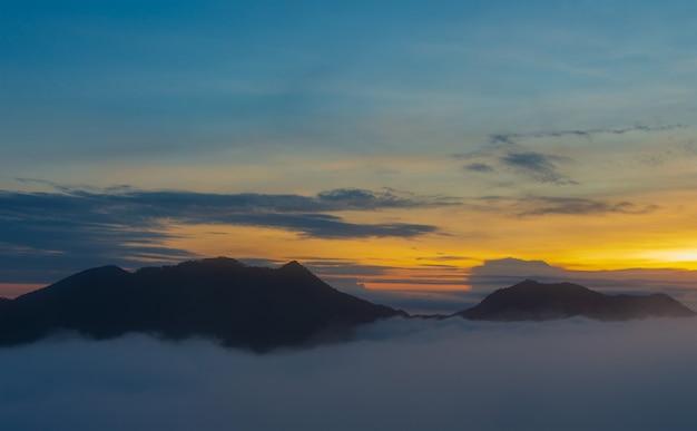 山の景色の朝霧、美しい霧と日の出の光。