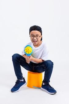 アジアの少年が白い背景の上の噴出銃