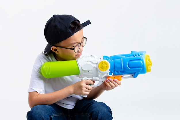 アジアの少年が白い背景の上の噴出銃で遊んで