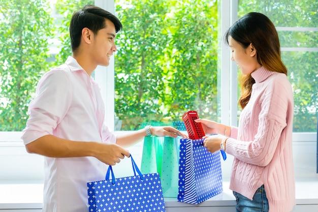 若い男がガールフレンドに買い物袋にプレゼントを与える