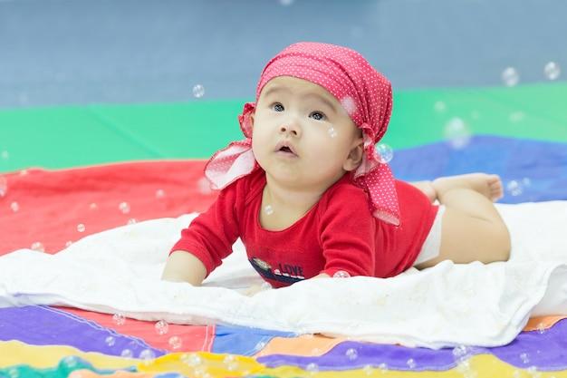 空気中のバブルを見ているアジアの赤ちゃん